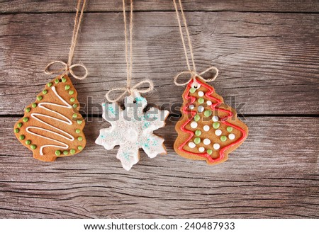 Gingerbread cookie hanging over a wooden background in a christmas theme