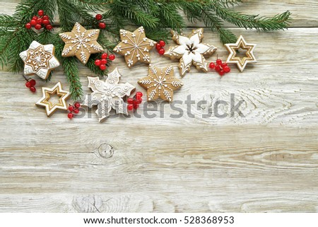 Gingerbread cookies  with christmas tree, red berries  on wooden table