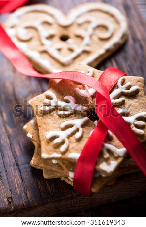 Gingerbread cookies with red ribbon on rustic wooden background