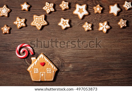 Gingerbread House cookie with candy cane and stars over a wooden background.