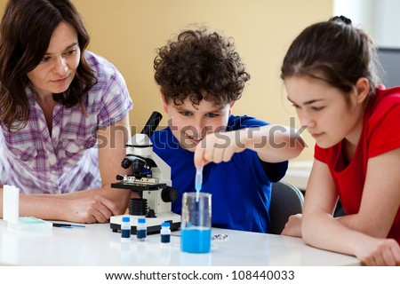 Girl and boy examining preparation under the microscope