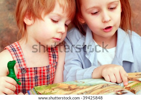 girl and boy friendly reading an interesting book