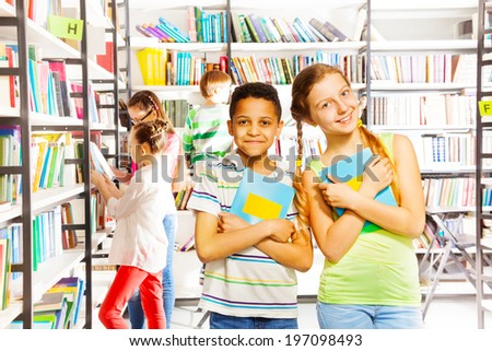 Girl and boy with books together in library
