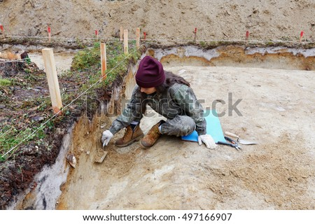 Girl archaeologist cleans a wall in the excavation