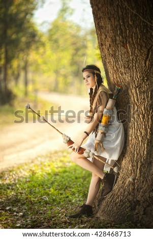 Girl archer with the wooden bow in traditional costume suit and fur hat. Summer forest on the background.