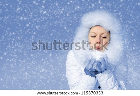 Girl blows off snowflakes from the hand. Blue sky, falling snow