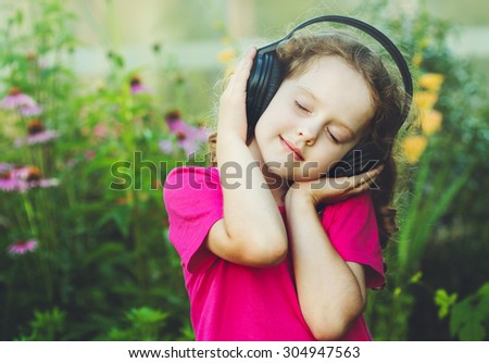 Girl closed her eyes and listen to music on headphones. Instagram filter.