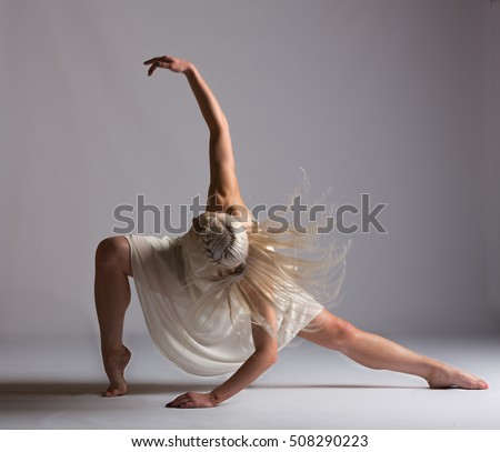 Girl contemporary dancer in studio against a white background in creme colored dress
