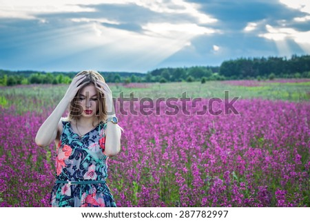 Girl coyly touches the hair. Girl in the field with wildflowers.