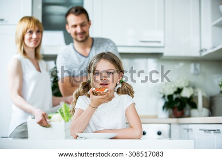 Girl eating bread with tomato and chive in kitchen
