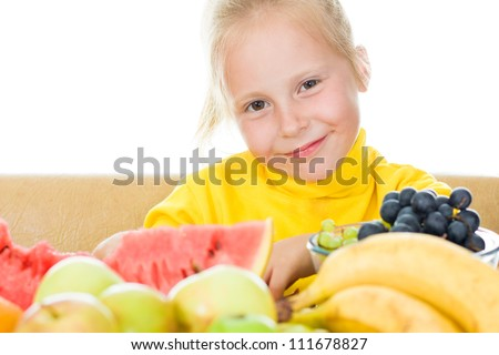 Girl eats fruit on a white background.