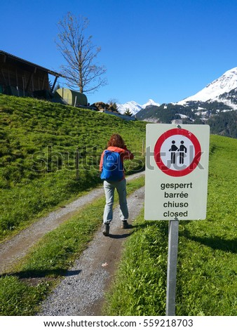 girl entering area forbidden for walk by sign in mountains