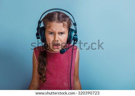 Girl European appearance decade listening to music with headphones open mouth on a blue background