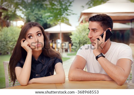 Girl Feeling Bored while her Boyfriend is on The Phone - Woman and man on a boring date ignoring rules of politeness
