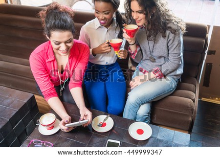 Girl friends sitting together in cafe and showing photos on tablet PC