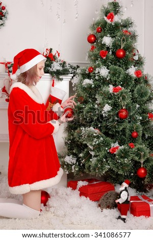 girl hangs up the ball on a white Christmas tree