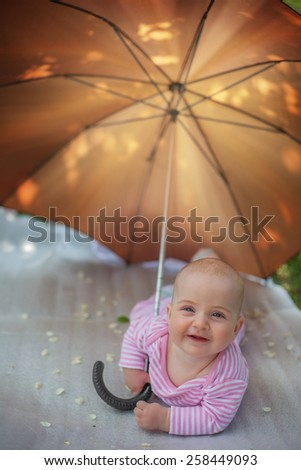 girl hiding from the sun under an umbrella