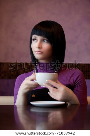 girl hold cup of coffee in hand thoughtful