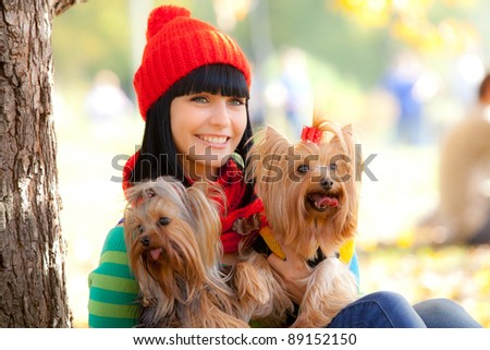 girl holds two small dog in hands