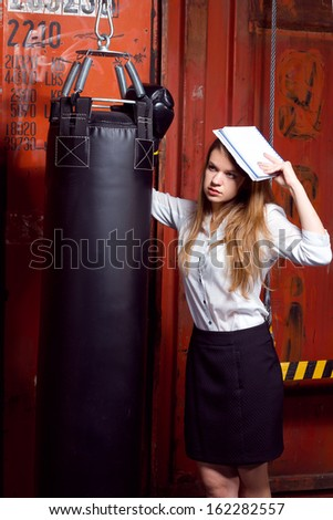 Girl in a business suit with papers near the punch bag
