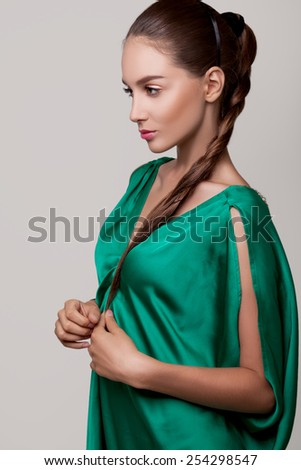 Girl in a green dress. Beautiful slim girl model in a green dress and dark hair.People, beauty, spa, cosmetology and relaxation concept - close up of beautiful young woman