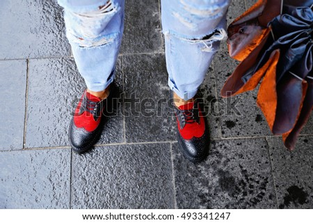 Girl in a light blue ripped jeans and stylish red and blue boots made of suede and leather. A woman walking in the rain. Women's legs and orange umbrella.
