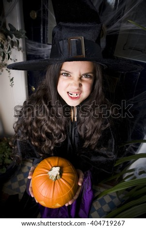 Girl in a witch's costume at a Hallowe'en party, holding a pumpkin