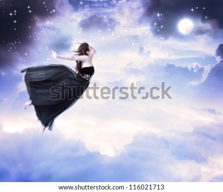 Girl in beautiful black dress jumping in the moonlight sky (serenity)