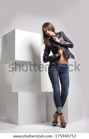 girl in black leather jackets, biker jacket posing in studio on large white cubes
