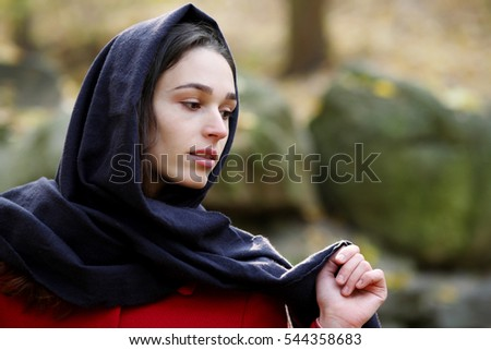 Girl in black scarf walks in autumn park.