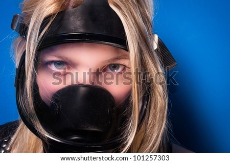 Girl in gas-mask against blue wall