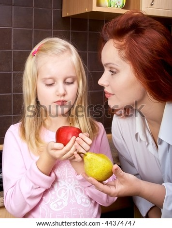 Girl in kitchen holding an apple and looked at him, her mother offers her a pear