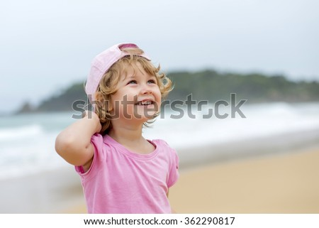 girl in pink shirt and hat at the beach