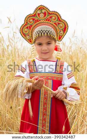 Girl in Russian national sundress standing in a wheat field and holding ears of corn