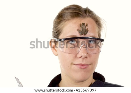 Girl in Science class wearing goggles getting ready to dissect a frog as it climbs on her face, white background
