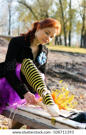 Girl in striped stockings tying Pointe shoes