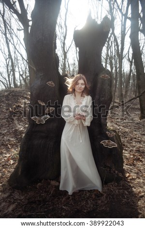 Girl in vintage dress in the sleeping forest with a giant moth.