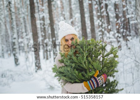 girl in winter forest holds branches in his hands