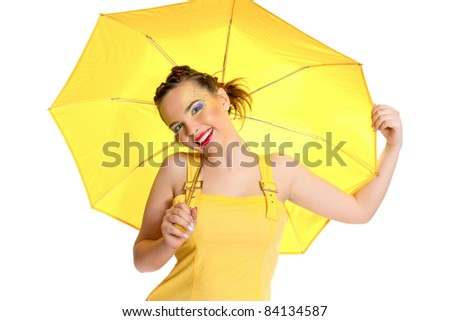 Girl in yellow dress with a yellow umbrella posing on a white background