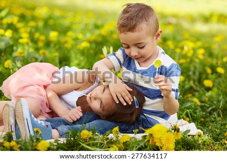 Girl lying with the boy in a blossoming orchard