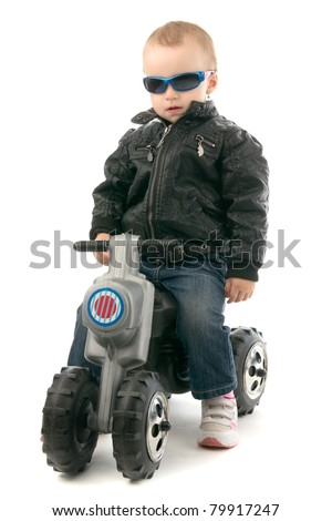 Girl on child's motorcycle in leather jacket and with glasses, on whites background.
