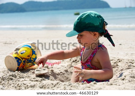Girl plays on the sand with the toys. Thailand