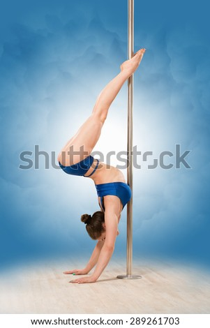 Girl pole dancing in dance hall. Young pretty girl performing partly undressed, i.e. in navy blue underwear.