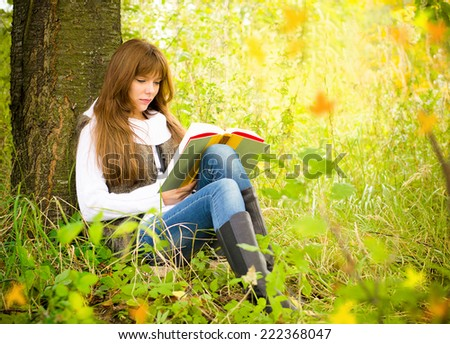 Girl reading a book on nature near a tree