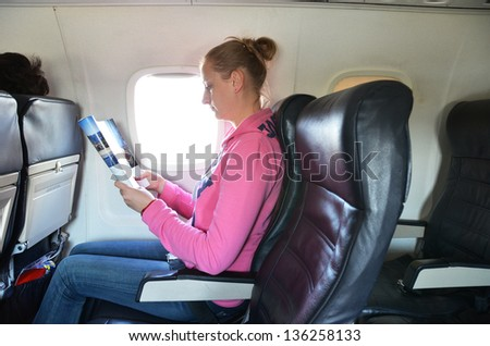 Girl reading a magazine in the airplane
