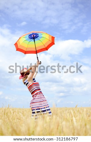 Girl rising umbrella and standing in golden wheat field. Women holding red hat to protect from wind over blue sky outdoors background