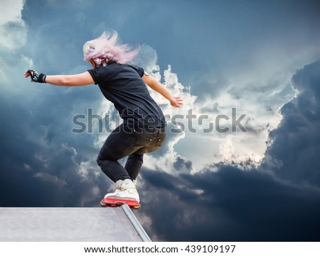 girl roller performs a trick against the sky