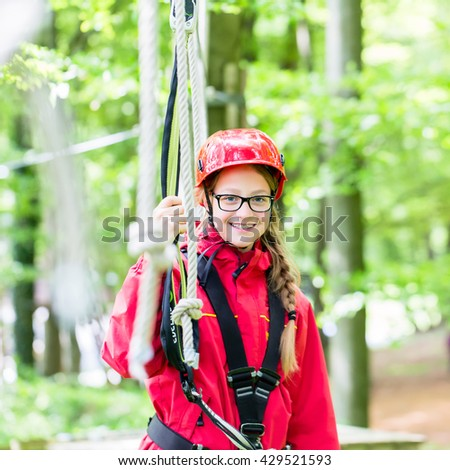 Girl roping up in high rope course exercising the necessary safety precautions