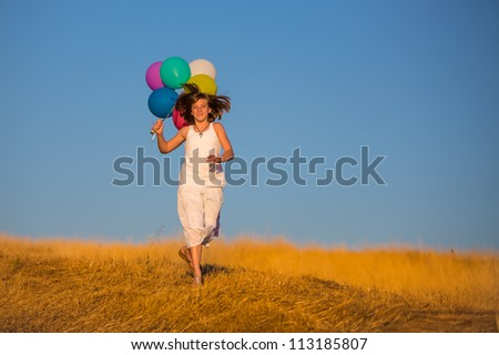 Girl running with balloons