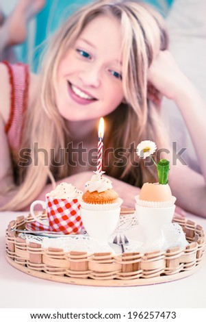 Girl's birthday breakfast in bed. With little cupcake, burning candle and hot chocolate. In the background happy girl. Toned image. Selective focus on candle.